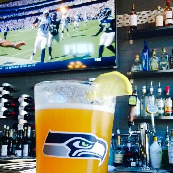 Seahawks glass of beer with sports playing in the background